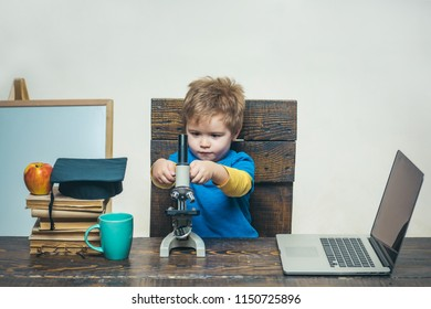 Science. Biology. Experiment. Education. Study. Thoughtful smart boy working with microscope and laptop. Little kid in graduation hat with microscope. Modern technology.
