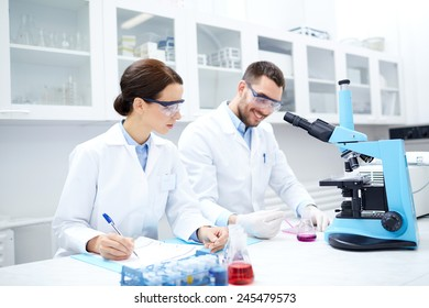 science, chemistry, technology, biology and people concept - young scientists with microscope and samples making test or research in clinical laboratory and taking notes