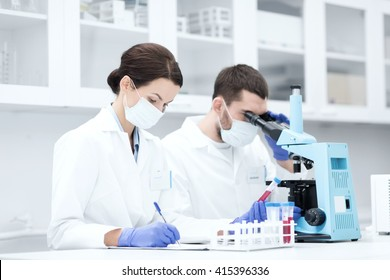 science, chemistry, technology, biology and people concept - young scientists with test tube and microscope making research in clinical laboratory and taking notes