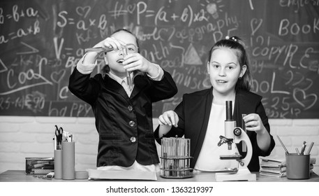 Science concept. Gymnasium students with in depth study of natural sciences. Private school. School project investigation. School experiment. Girls school uniform busy with proving their hypothesis.