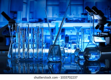 Science Concept. Laboratory Research and Development. Scientific glassware for chemical experiment. Microscope, laboratory beakers, test tubes, pipettes. Lab interior background.