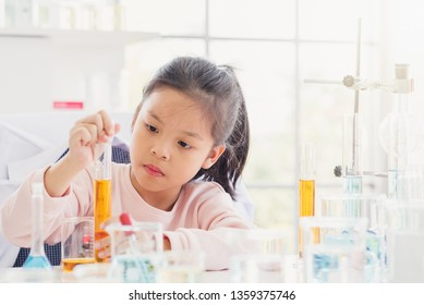 Science and education concept,Girl doing experiments in the laboratory.Little chemist holds scientific experiment ,Science and education concept
