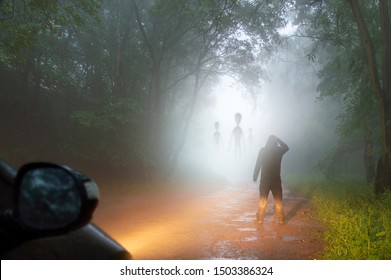 A science fiction concept of a man looking at aliens coming out the mist on a foggy, spooky forest road in the evening. Highlighted by car headlights.