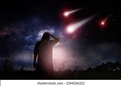 A science fiction edit of a man standing in a field as meteorites speed towards the earth at night with the stars in the sky