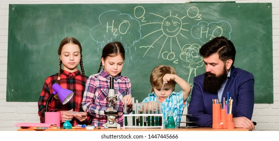 Science involves theory. School chemistry experiment. Explaining chemistry to kids. Fascinating chemistry lesson. Man bearded teacher and pupils with test tubes in classroom. School chemistry lab.