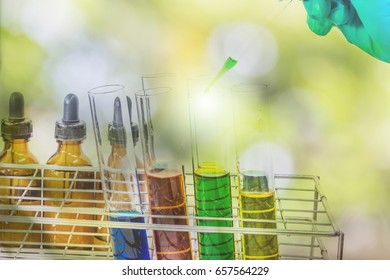 Science laboratory test tubes.Double exposure of scientist hand holding laboratory flask.Pipette adding fluid to one of several test tubes.