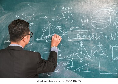 The science professor writes on the board while having a blackboard and a blackboard.