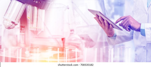 Science research and technology concept - Scientist holding tablet computer with scientific instrument, microscope and chemical test tube in lab background.