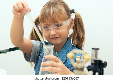 Science school, Workshop. A girl child collect molecules and conduct chemical experiments. On the table is a robot. STEM education. Science and technology.