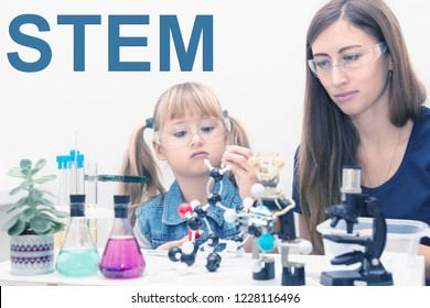 Science school, Workshop. A woman teacher and girl child collect molecules and conduct chemical experiments. On the table is a robot. STEM education.