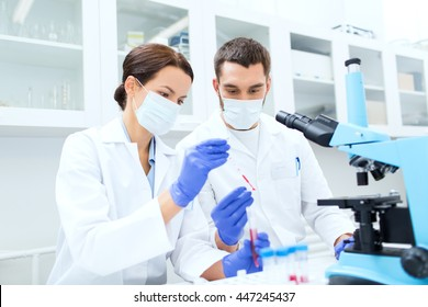 science, technology, biology and people concept - young scientists with pipette, test tube and microscope making research in clinical laboratory