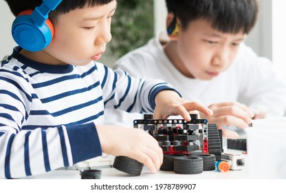 Science, Technology, Engineering and Mathematics (STEM) education concept. Two smart looking Asian young kids with headphone assemble and test a robot with EV3 components as school project at home.