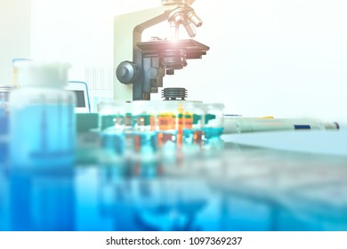 Scientific background with light microscope and histological samples on working table out of focus. This image is toned.  Space for your text
