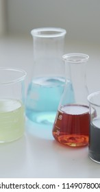 Scientific Beaker and Conical Flasks Filled With Pastel Coloured Liquids