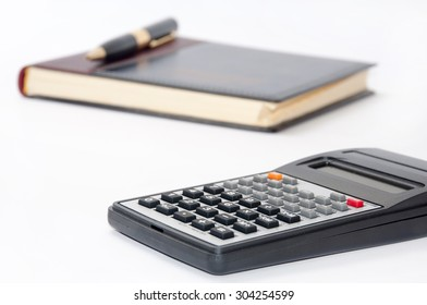 Scientific calculator and golden pen on business notebook.