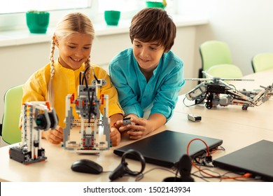 Scientific experiment. Smart boy helping his smiling classmate turning on a robot made of construction set at the lesson.