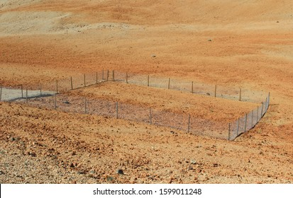 Scientific experimental plot fenced among dry arid hot landscape along the hiking trail on a climbing trekking up to the Mount Teide via Montana Blanca Mountain, Tenerife, Canary Islands, Spain.