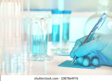 Scientific, medical or education background. Biological or biochemical lab out of focus, closeup on gloved hand writing a note. Focus on the hand.