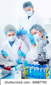 Scientific people working with a microscope in lab.