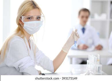 Scientific research team with clear solution in laboratory - Shutterstock ID 393173149