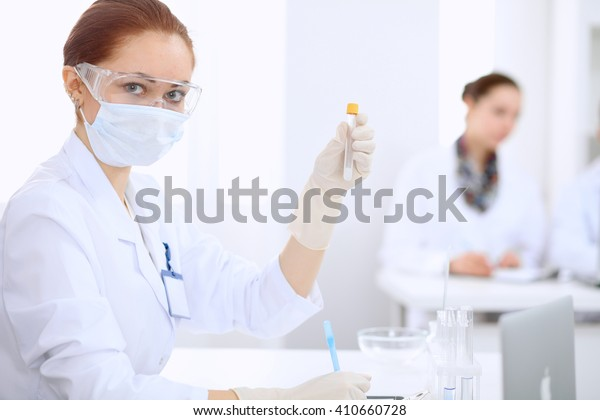 Scientific research team with clear solution in laboratory