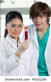 Scientific researchers looking at a liquid solution.