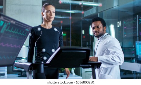 In Scientific Sports Laboratory Beautiful Woman Athlete Walks on a Treadmill with Electrodes Attached to Her Body, While Black Scientist Looking at Her, Monitors Show EKG Data on Display.
