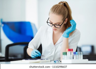 Scientist analyzing microscope slide at laboratory. Female Working in Laboratory With Microscope. Researcher examining slide. Concenrated doctor working with microscope in laboratory