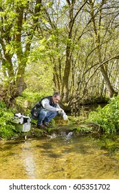 Scientist and biologist hydro-biologist takes water samples for analysis. / View of a Biologist take a sample in a river.