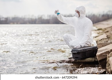 Scientist or biologist wearing protective uniforms examining the liquid contents of a test tube. Ecology and environmental pollution concept.