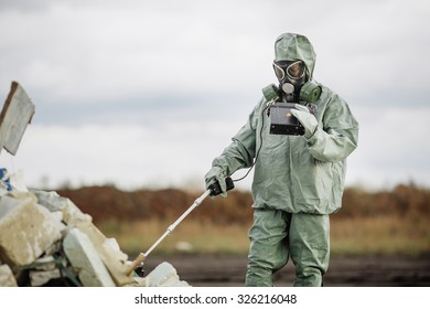 Scientist dosimetrist (radiation supervisor) in protective clothing and gas mask with geiger counter checks the level of radioactive radiation in the danger zone