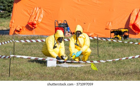 Scientist dosimetrist with radiomerter and radiation supervisor in protective clothing and gas masks take samples of radioactive material in radioactive zone, Sofia, Bulgaria, November 6, 2015.