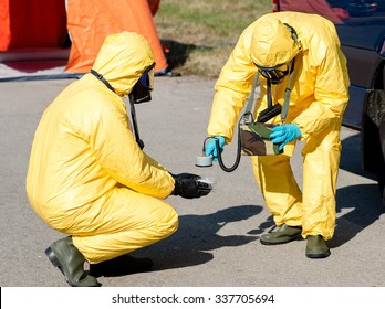 Scientist dosimetrist with radiometer and scientist radiation supervisor in protective clothing and gas masks examine a  sample of radioactive material in hazardous radioactive zone.