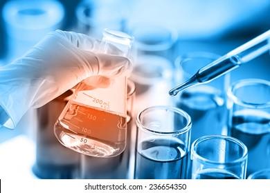 Wissenschaftler, der das Reagenz in das Reagenzglas für die Reaktionsprüfung im chemischen Laboratorium wirft.