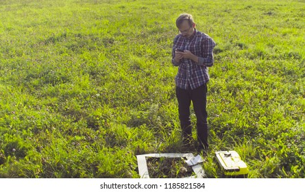 Scientist ecologist standing on the meadow and checking with the GPS navigator. Next to him there is a square marking site. Field work
