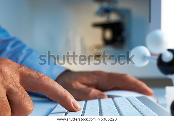 Scientist entering data into computer selective foucs