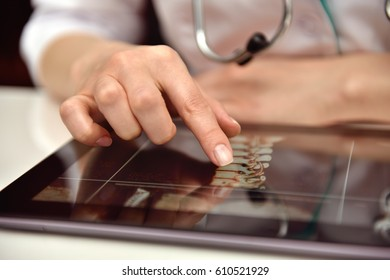 Scientist  Examines An X-ray Of Patient On Touch Pad. healthcare and medical concept