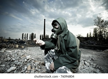 Scientist with gas mask examining rock in destroyed territory after explosion