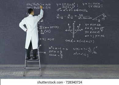 Scientist of genius standing on a ladder writing complex mathematical formulas with white chalk on large blackboard.