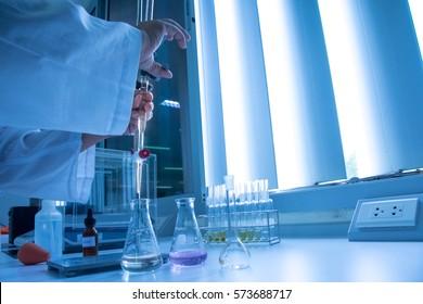 Scientist hand setting up buret or burette in science laboratory