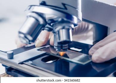 Scientist hands with microscope close-up shot in the laboratory