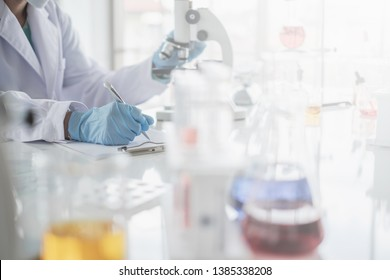 A scientist hands writing on a clipboard in laboratory with test tube microscope and solutions.