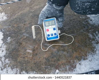 Scientist holding Electronic thermometer measuring volcanic soil temperature with probe stick in the ground