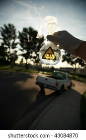 a Scientist holds a 500ml beaker filled with CO2 against the blue sky, with a truck in the background representing carbon emmissions from vechiles
