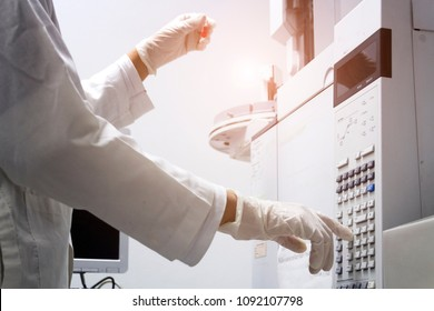 scientist holds an amber vial and press the control button of GC chromatography