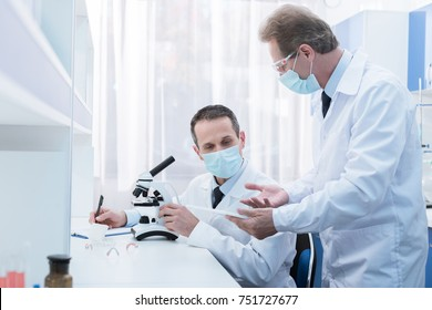 Scientist in lab coat and sterile mask doing microscope analysis and talking to a colleague
