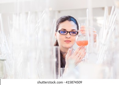 A scientist in a laboratory studying the liquid in the beaker