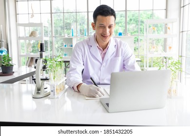 scientist looking at laptop computer and writing notes in a laboratory