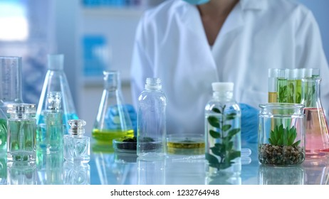 Scientist looking at liquid herbal extracts in bottle, organic perfumery testing