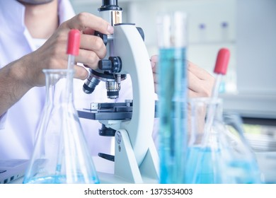 scientist scientist looks through microscope , in laboratory room, near colorful liquid in beaker progress result of lab testing and record data in laptop.